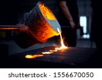 Small photo of foundry. Steel foundry. Molten iron pour from ladle into melting furnace ; foundry porcess