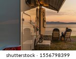 Campground Pitch Scenery. RV Camper Van In the Recreational Vehicles Park. Woman Relaxing on a Chair in Front of Her Camper Van. - stock photo
