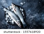 Fresh raw seabass fish on black ...