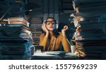 Small photo of Careless lazy female employee sitting at office desk and listening to music instead of working, she is surrounded by piles of paperwork