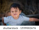Small photo of A little boy expressing resentful and uncooperative attitude by making an upset face and confontational body stance.