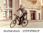 Small photo of Happy manhood. Delighted man keeping smile on his face while riding his bicycle