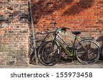 Bicycles on the pavement near brick wall in Brugges, Belgium  - stock photo
