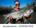 Small photo of Fisherman holds the big Asp (Leuciscus aspius) and smiles