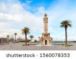 Konak Square view with palm trees and old clock tower, it was built in 1901 and accepted as the official symbol of Izmir City, Turkey