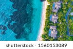 Tropical island bure accommodation in resort with reef and turquoise water and rocky outcrop Aerial shot from above. Fiji island Kokomo luxury resort. Palm trees overlooking Pacific Ocean in summer
