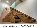 Small photo of Modern architecture interior with luxury hallway with glossy wooden stairs in multi-storey house. Custom built pullout cabinets on glides in slots under stairs. Use of space for storage.