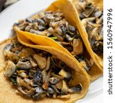 "Small photo of Traditional mexican corn smut taco called ""huitlacoche"" on wooden background"