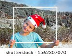 Small photo of Charming boy in a clownish cap of Santa Claus smiles through a white frame. Magnificent panorama of Giau Pass, Dolomite Alps. The first snow. Concept of Christmas and New Year tourism