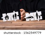Small photo of Jigsaw Puzzles Showing Separation Of Family With House And Car Divided By Person's Hand