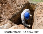 Man In Blue Cap Digs Grave At...