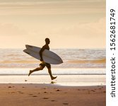 Surfer On The Beach Running...