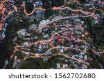 Overhead aerial drone shot view of winding mountain road street light on Monte Bre in Lugano, Switzerland