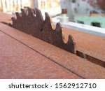Small photo of Rusty surfaces of old woodworking machine. A huge antediluvian cutter protrudes from a small slot on the frame seized by corrosion. Copy space. Close-up, shallow focus