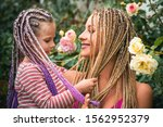 Small photo of Happy smiling mother with her little daughter with plaits. Hair in trendy weave plait. Lifestyle portrait mom and daughter in happy mood at the outside