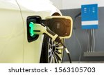 Power supply connect to electric car for add charge to the battery. Charging re technology industry transport which are the future of the Automobile with station charge on background - stock photo