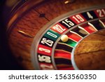 Roulette wheel with a white ball on green at zero number in a casino - stock photo