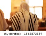 Small photo of Orthodox ultra Orthodox Jew from a tallit in the synagogue. rear view of an orthodox Jew in the mantle, a bit in the synagogue
