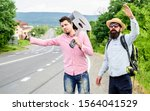 Small photo of Travel by autostop. Hopeless hitchhiker. Company friends looking for transport. Men try stop car. Travelers with backpack and guitar ready strat new journey. Hitchhiker meet friend at road.