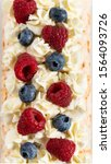 Small photo of Meringue roll cake with cream, Blueberries and raspberries. Roulade, summer dessert. Texture, close up. Confectionery, menu