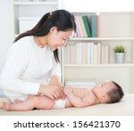 asian mother changing diaper to ... | Shutterstock . vector #156421370