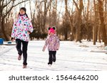 Small photo of Mother and little girl in colored jackets jogging by snow in winter park. Concept of instill sports health habits in children