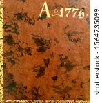 """AD 1776 (""""A[nn]o [Domini] 1776"""") embossed in brown leather and gilded – taken from an account book for that year"""