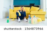 Small photo of Enfeebled young female worker of the cleaning service sitting near the couch and feeling tired after washing floor on cuisine.