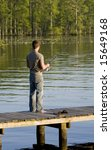 Man Fishing Off Of A Dock Into...