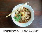 Small photo of Instant noodle pork with thicken Soup.Top view of a white bowl of Thai pork thicken soup noodle with ,braised pork, sliced pork,meatball,on wooden table.Noodles are fast food.Thai street food market.