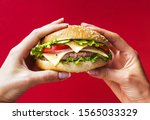 woman holding tasty burger in...