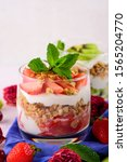 Small photo of close up vertical image of dessert with strawberries, kiwi, cream, granola and mint. trifle concept