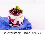 Small photo of close up dessert trifle with cherries, Greek yogurt and granola in glass on blue cloth napkin on light pink background with copy space. berry dessert concept