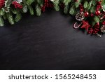 Small photo of Christmas background concept. Top view of Christmas gift box red balls with spruce branches, pine cones, red berries and bell on black wooden background.