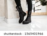 Young trendy woman in black stylish jeans in fashionable leather lace-up boots stands on the white tile in the mall. Fashion collection of women