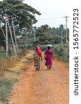 Two Women Walking By Carrying...
