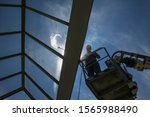worker of Professional Facade Cleaning Services washing a galss roof - stock photo