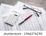 Small photo of Taxes calculation concept. Financial documents, calculator, glasses on grey background