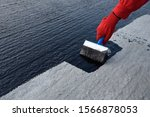 Small photo of Roofer cover the concrete base, polymer modified bitumen waterproofing primer. A worker brushes cover concrete, bitumen-rubber primer