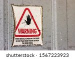 Small photo of Worn out 'warning' sticker attached to door. It is a warning about manually opening the garage door using only the rope to pull down.