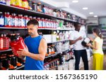 Small photo of Interested athletic man choosing food supplements in large assortment of sport nutrition store