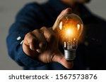 a businessman holding a light... | Shutterstock . vector #1567573876