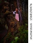 Woman in big old mossy tree holding a bird on her hand and the other bird flying to her. Ancient cypress grove in Oregon near Salem.  Silver Falls Park. USA