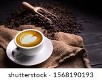 Small photo of Cup of coffee latte with heart shape and coffee beans on old wooden background