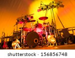 angled view of a rock band stage setup with drums, guitars and spotlights - stock photo