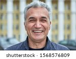 Small photo of Closeup laughing face of an elderly businessman, civil servant, doctor or television presenter. Portrait of a joyful caucasian man over fifty years, with short gray hair outdoors, near public building