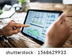 Small photo of Close-up Of Businessman Analyzing Stock Market Status On Digital Tablet