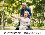 Small photo of senior asian man walking in park with wheelchair bound wife