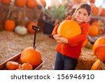 Cute Girl Choosing A Pumpkin A...
