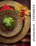 Restaurant autumn table setting. Place setting with oriental plates and autumn decoartion. - stock photo